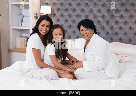 Portrait of multi-generation family sitting on bed at home - Stock Photo