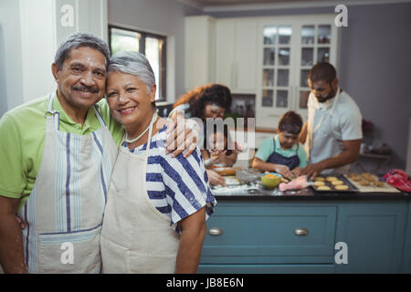 Senior couple smiling at camera while family members preparing dessert in background at home - Stock Photo