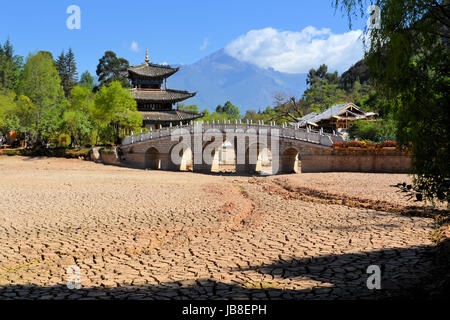 during a drought in China, cracks in the soil are showing in a river bed due to global warming - Stock Photo