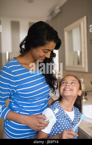 Smiling girl with mother holding toothbrushes in bathroom - Stock Photo