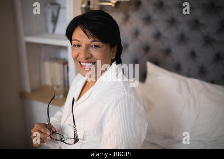Portrait of smiling mature woman sitting on bed at home - Stock Photo