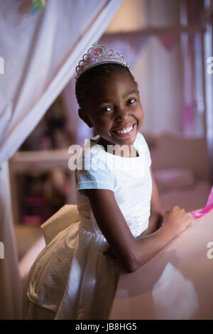 Portrait of cheerful girl wearing crown while standing at home - Stock Photo