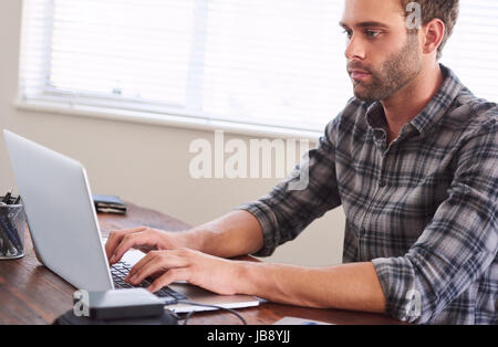 Young adult man looking frustrated and fed-up with work, while still typing on his notebook, seated at his wooden - Stock Photo
