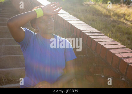 Tired woman standing with hand on forehead in the boot camp on a sunny day - Stock Photo