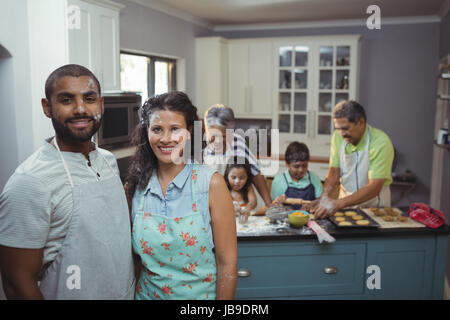 Couple smiling at camera while family members preparing dessert in background at home - Stock Photo
