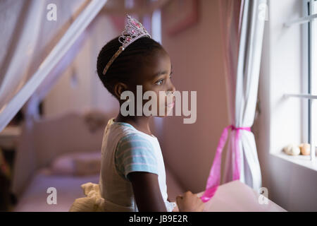 Side view of thoughtful girl wearing crown standing in bedroom at home - Stock Photo