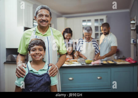 Grandfather and grandson smiling at camera while family members preparing dessert in background at home - Stock Photo