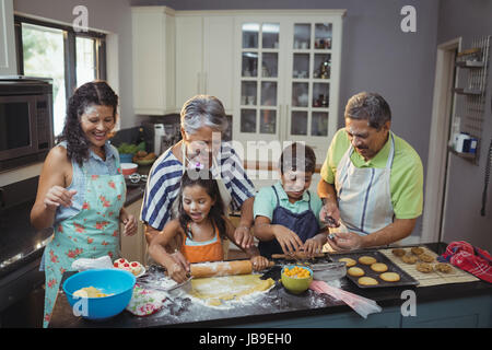 Happy family preparing dessert in kitchen at home - Stock Photo