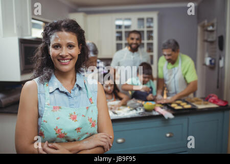 Woman smiling at camera while family members preparing dessert in background at home - Stock Photo