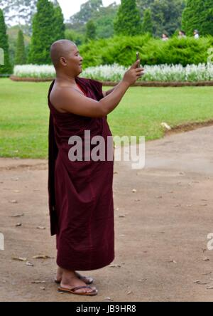 A Buddhist monk in maroon robes stands taking a selfie with his mobile phone in a Myanmar park - Stock Photo