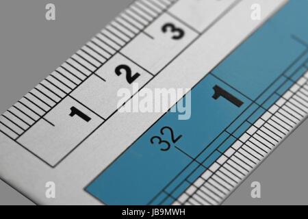 Aluminum graduated ruler closeup on gray background. - Stock Photo