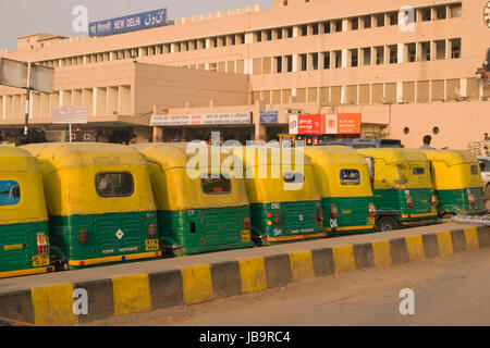 Row of yellow auto rickshaws outside New Delhi railway station in Delhi, India. - Stock Photo