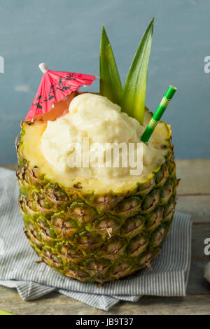 Frozen Pina Colada Cocktail in a Pineapple with a Garnish - Stock Photo