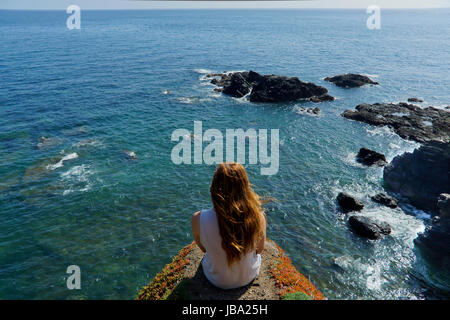 A young woman looks out over the sea from Lizards Point in Cornwall, UK - Stock Photo