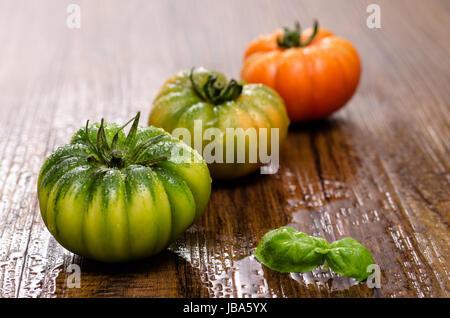 Italienische Ochsenherz-Tomaten mit Basilikum auf einem Tisch aus Holz - Stock Photo