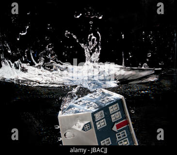 Toy house sinking underwater on a black background - Stock Photo