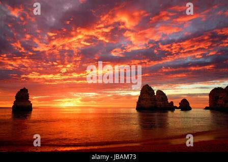 Sonnenaufgang mit intensiven Farben am Meer, mit Felsen und roten Wolken - Stock Photo