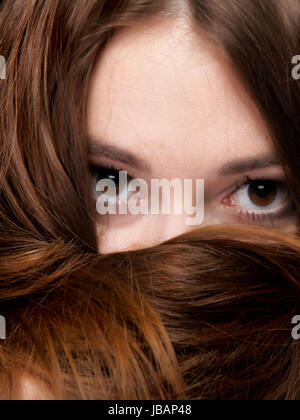 Close-up portrait of a beautiful woman covers the face by long brown hairs