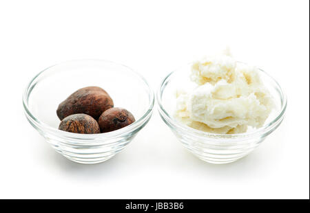 Shea butter and nuts in glass bowls isolated on white - Stock Photo