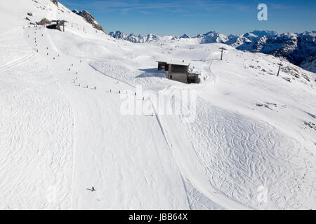 Mit Schnee bedeckte Skipiste mit Skifahrern und Snowboardern in den Bergen Alpen - Stock Photo