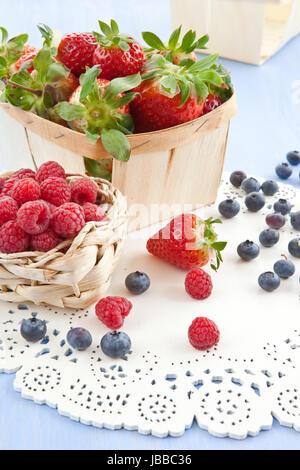 Frische Erdbeeren, Himbeeren und Blaubeeren auf blauem Hintergrund - Stock Photo