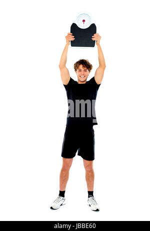 Male athlete standing and showing weighing machine against white background - Stock Photo