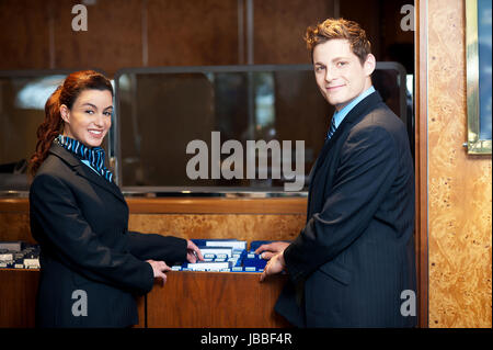 Casual shot of young help desk executives checking customer records while posing in front of camera - Stock Photo