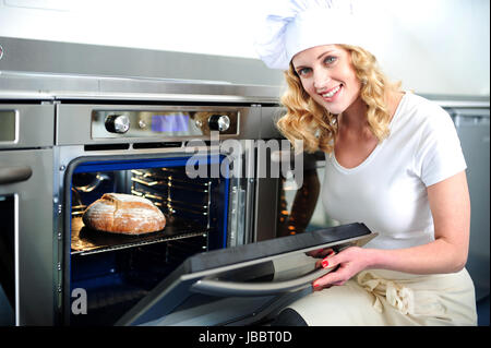 Pretty baker opening an oven door. Ready to pull out baked bread - Stock Photo