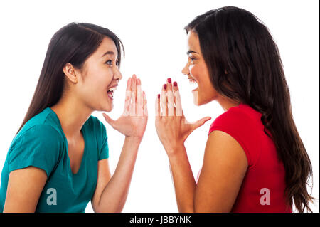 Young girls gossiping and sharing their secrets - Stock Photo