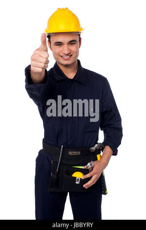 Handsome man in yellow safety helmet and construction worker uniform - Stock Photo