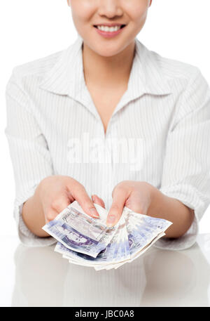 Cropped image of a young woman counting pounds currency - Stock Photo