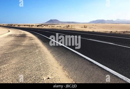 Winding road through the dunes of Corralejo with volcano in the background, in Fuerteventura, Canary Islands, Spain. - Stock Photo