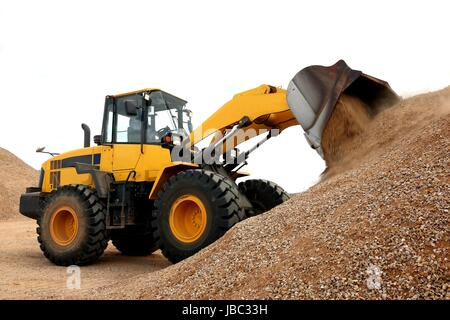 Bulldozer dumping stone and sand in a mining quarry - Stock Photo