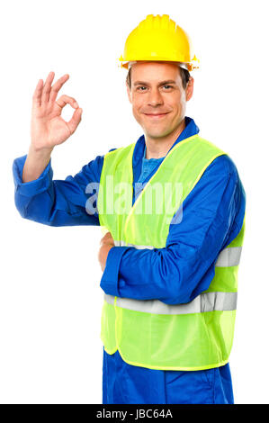 Handsome young worker gesturing okay sign in front of camera - Stock Photo