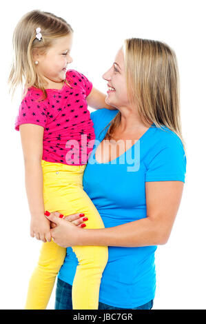Gorgeous mother holding her beautiful daughter in arms. Both engaged in jovial interaction - Stock Photo