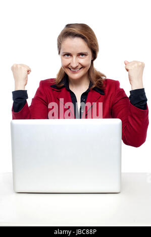 Smiling middle aged successful businesswoman pumping her fists. - Stock Photo