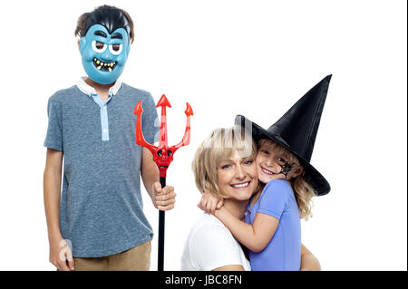 Mother hugging her daughter in witches hat while son wearing dracula face mask and holding pitchfork. - Stock Photo