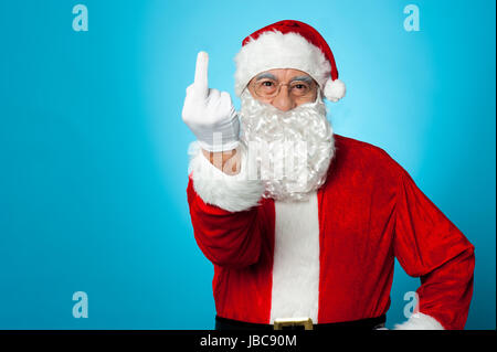Agitated Santa showing his middle finger to the camera - Stock Photo