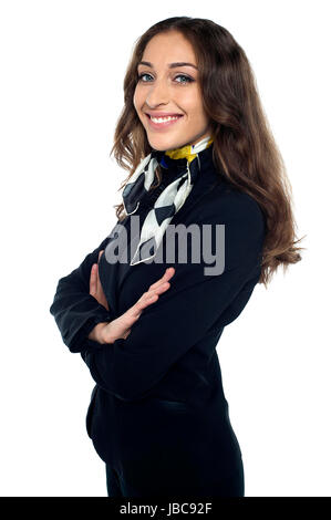 Casual shot of cheerful air stewardess standing sideways, arms folded. - Stock Photo