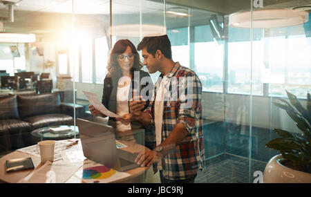 Young business people working together in creative workplace. Two creative professionals working on new project - Stock Photo