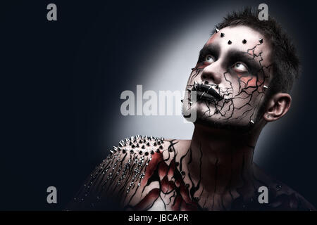 A creepy halloween makeup of a dark thoughtful moor with a peircing and scary body art. - Stock Photo