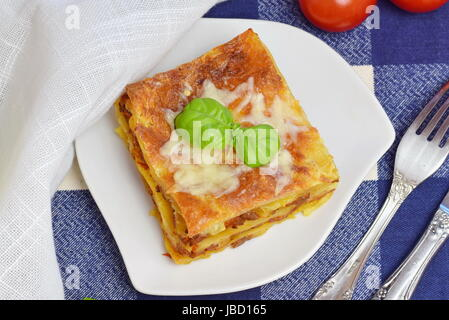 Slice of a home made lasagna with minced meat, tomato, cheese on a white plate. Healthy eating concept. - Stock Photo
