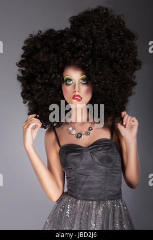 Extravagance. Eccentric Emotional Woman in Frizzy Fancy Wig with Braided Hairs