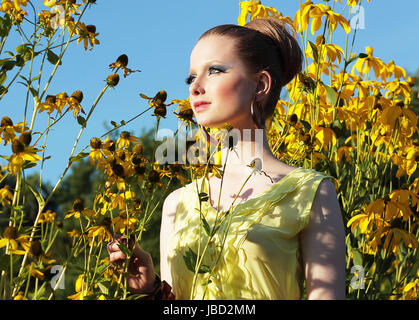 Summertime. Young Female in Meadow among Blooming Yellow Flowers - Stock Photo