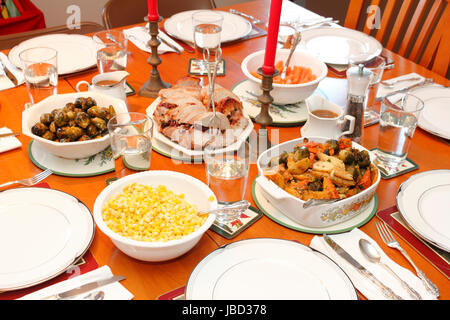 Festive dinner table set with dinnerware and bowls Christmas holiday favorite foods of fruit stuffed pork tenderloin, - Stock Photo
