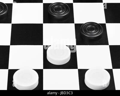 draughts game on black and white board close up - Stock Photo