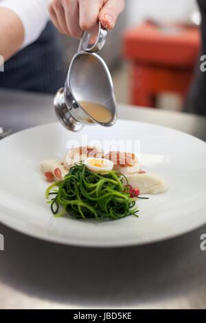 gourmet speise mit jakobsmuscheln und wachteleiern und püree angerichtet mit sauce - Stock Photo