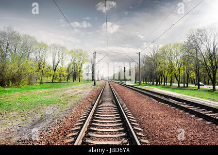 Gray cloudy sky over railroad in spring - Stock Photo