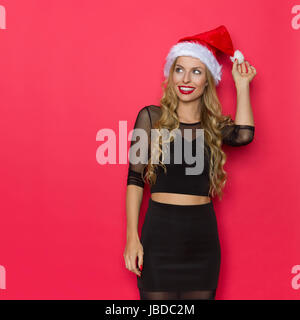 Smiling young blond woman in santa hat and black dress watching. Three quarter length studio shot on red background. - Stock Photo