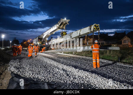 Rail construction workers laying new tracks - Stock Photo